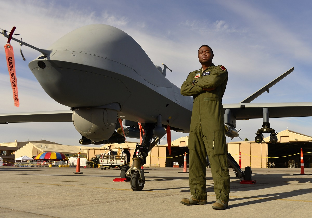 Staff Sgt. Kenneth, 432nd Wing MQ-9 sensor operator, stands in front of an MQ-9 Reaper during Aviation Nation Nov. 11, 2016, at Nellis Air Force Base, Nevada. Kenneth, along with many other maintenance, intelligence and aircrew members of Creech Air Force Base, Nevada, briefed spectators about the capabilities and basic functions of the MQ-9 Reaper and MQ-1 Predator. (U.S. Air Force photo by Senior Airman Christian Clausen/Released)