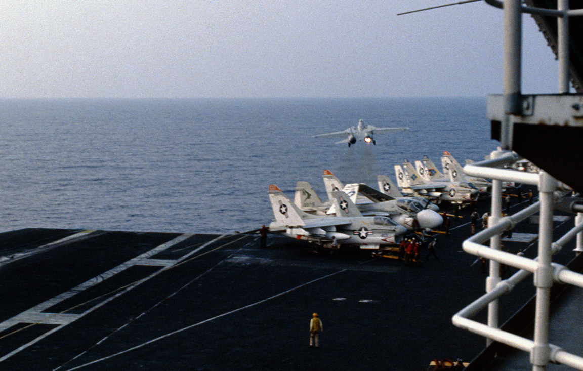An F-14A from VF-211 just seconds after losing one afterburner on a cat shot. Though not the incident in this story, the smoke trail and aircraft position relative to the ship are indicators of the effect of thrust asymmetry. In the story, Petro had to deal with loss of the engine (not just burner), and he used almost full rudder to compensate.