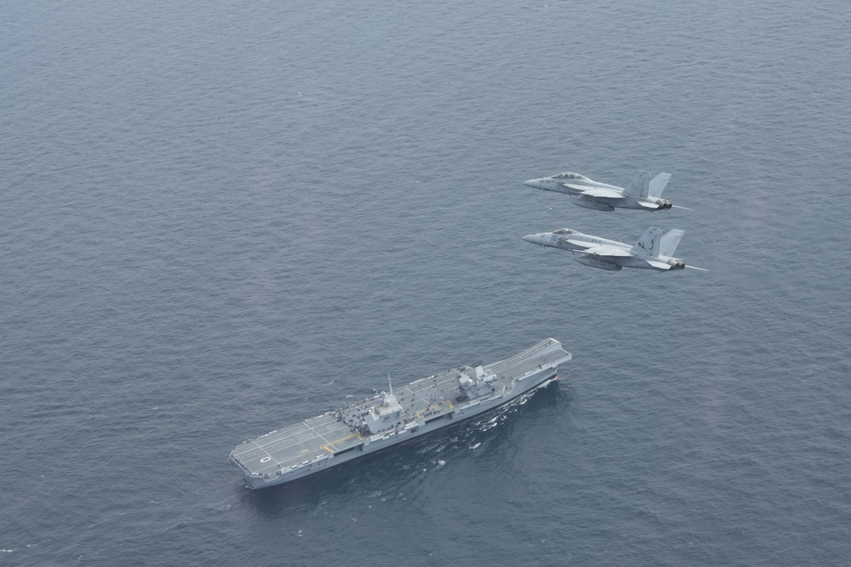 U.S. Navy F/A-18 Super Hornets fly above Royal Navy HMS Queen Elizabeth