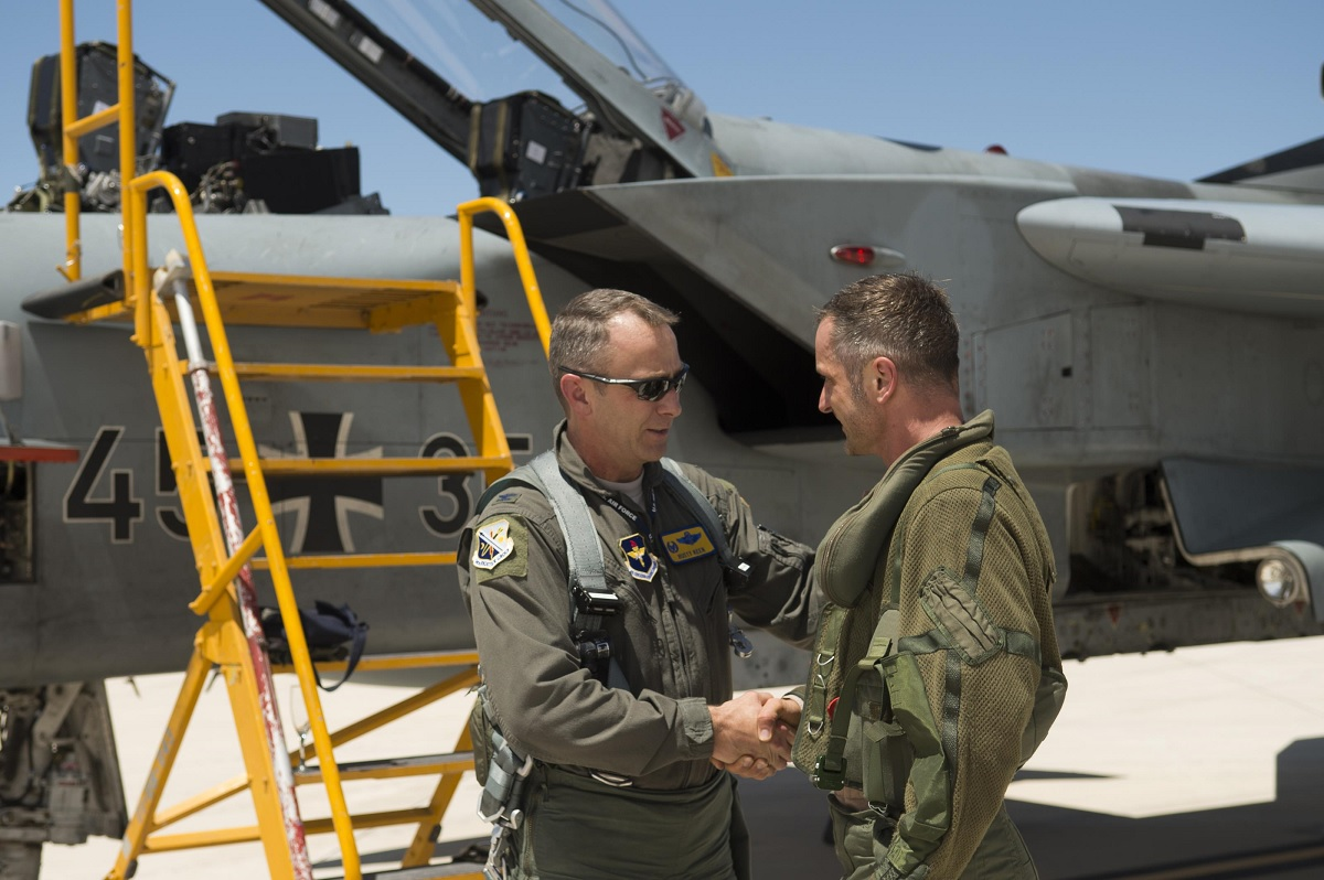 Col. James Keen, 54th Fighter Group commander, coins Maj. Lars Parlow, German air force Tornado pilot